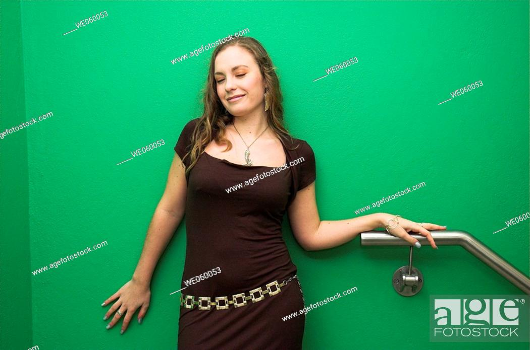 Stock Photo: Young female fashion model posing against a green wall.