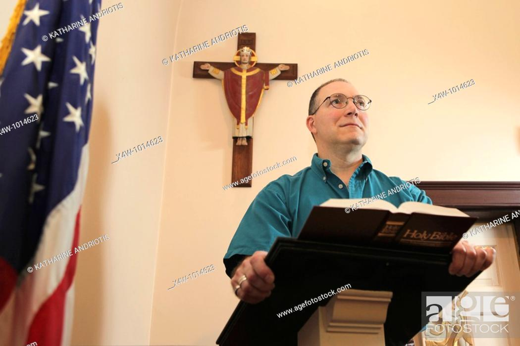 Imagen: Man at church pulpit preaching to congregation with American Flag and crucifix.