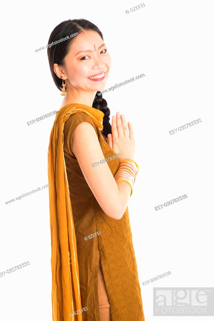 f123551828 Stock Photo - Portrait of young mixed race Indian Chinese female in traditional  punjabi dress greeting, standing isolated on white background.