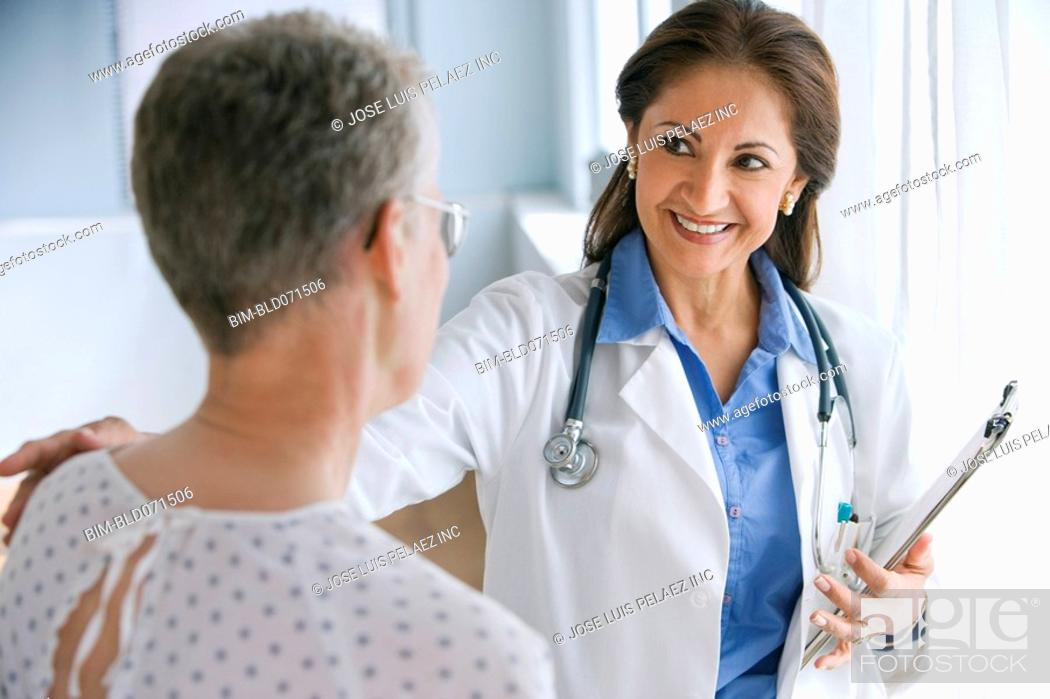 Stock Photo: Hispanic female doctor smiling at patient.