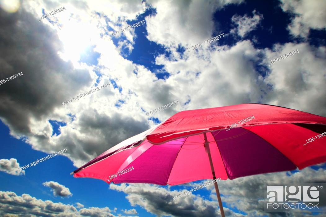 Stock Photo: a beach umbrella with clouds and the sun.