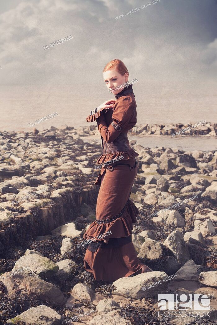 Imagen: Young woman in a victorian dress standing alone outdoors beside the sea.