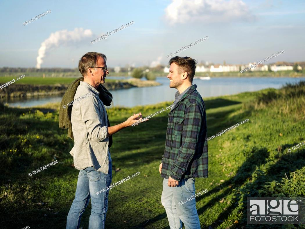 Stock Photo: Father talking with son while standing on grass at riverbank.