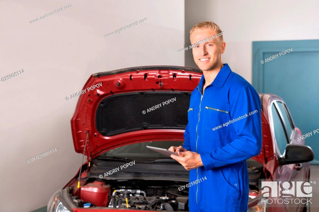 Stock Photo: Smiling Young Mechanic Using Digital Tablet In Garage.