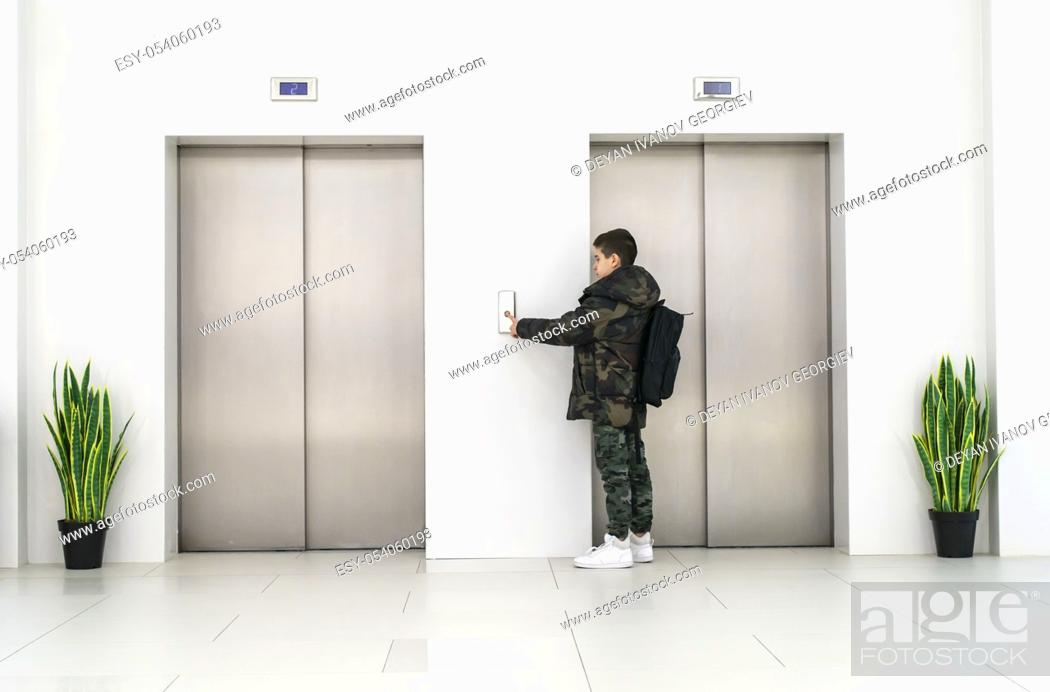 Stock Photo: Boy with casual clothes and white sneakers call the elevator. White contemporary building interior. Flowers in pots and white wall.