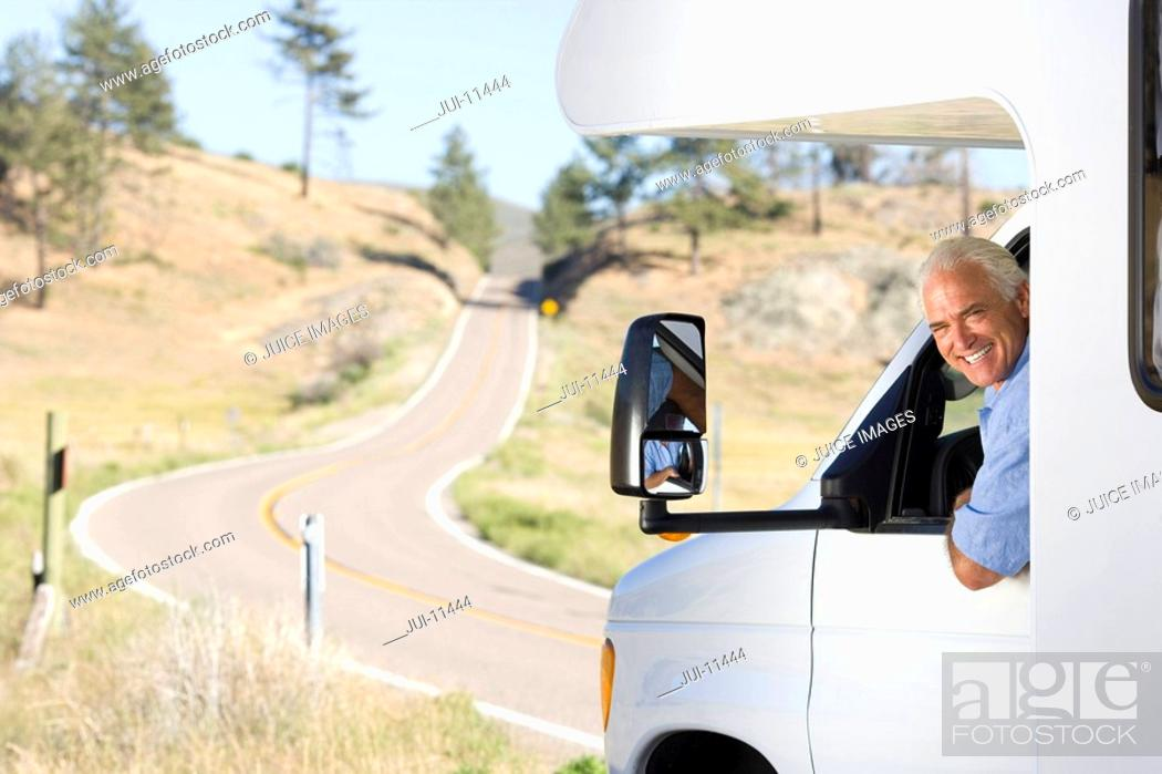 Stock Photo: Mature man leaning out of window of motor home, smiling, portrait.