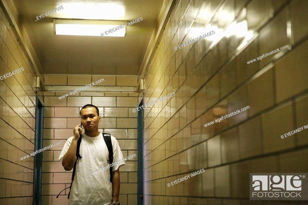 Stock Photo: Teenage boy 15-17 standing in passageway, on the phone.
