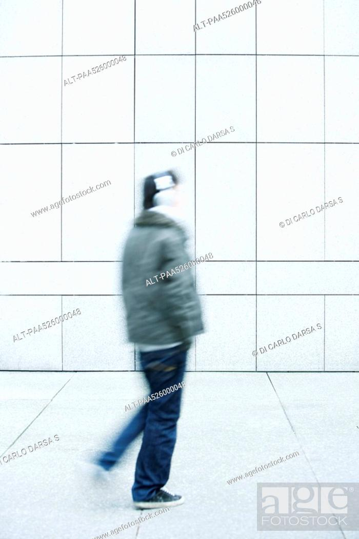 Stock Photo: Man walking with hands in pockets on sidewalk.