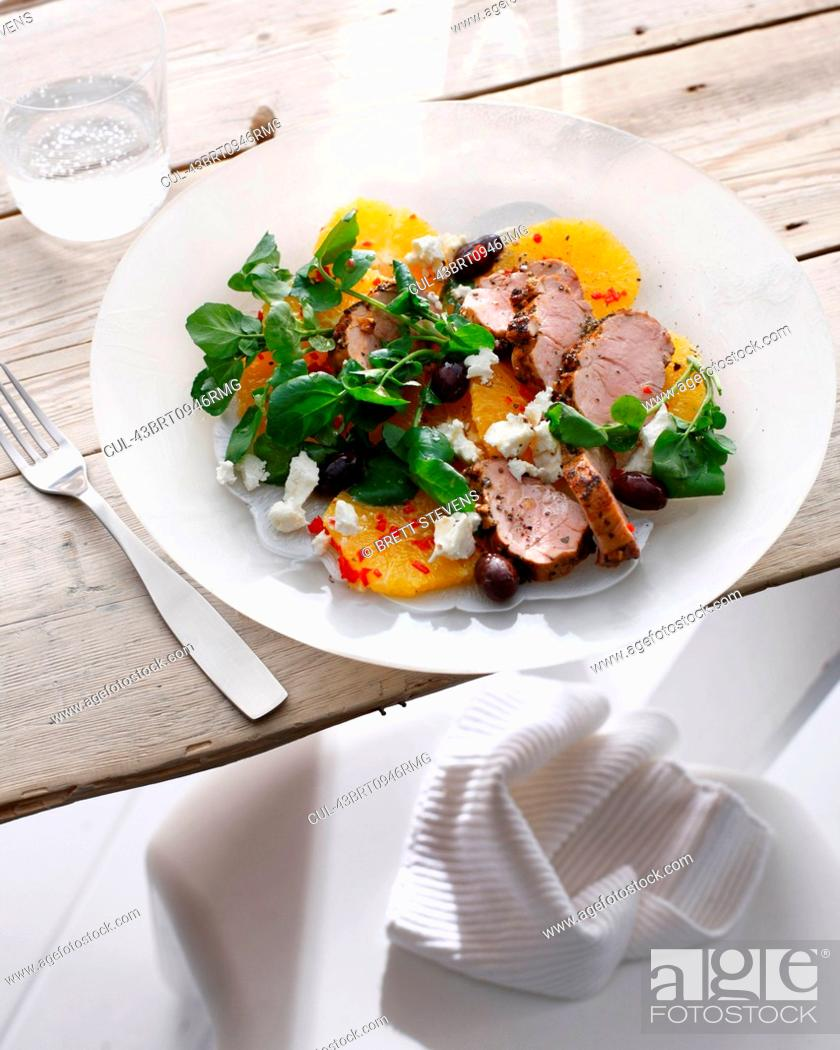Stock Photo: Plate of pork with pickled orange salad.