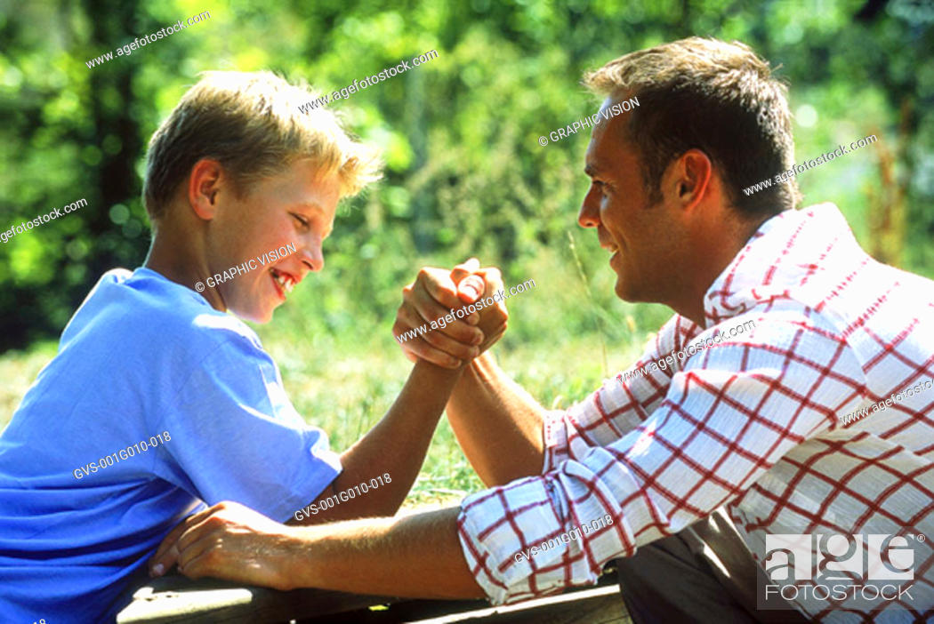 Stock Photo: Father and son playing arm wrestling.