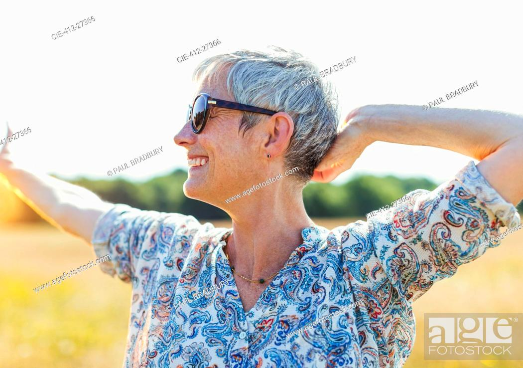 Stock Photo: Enthusiastic senior woman with arms outstretched in sunny field.