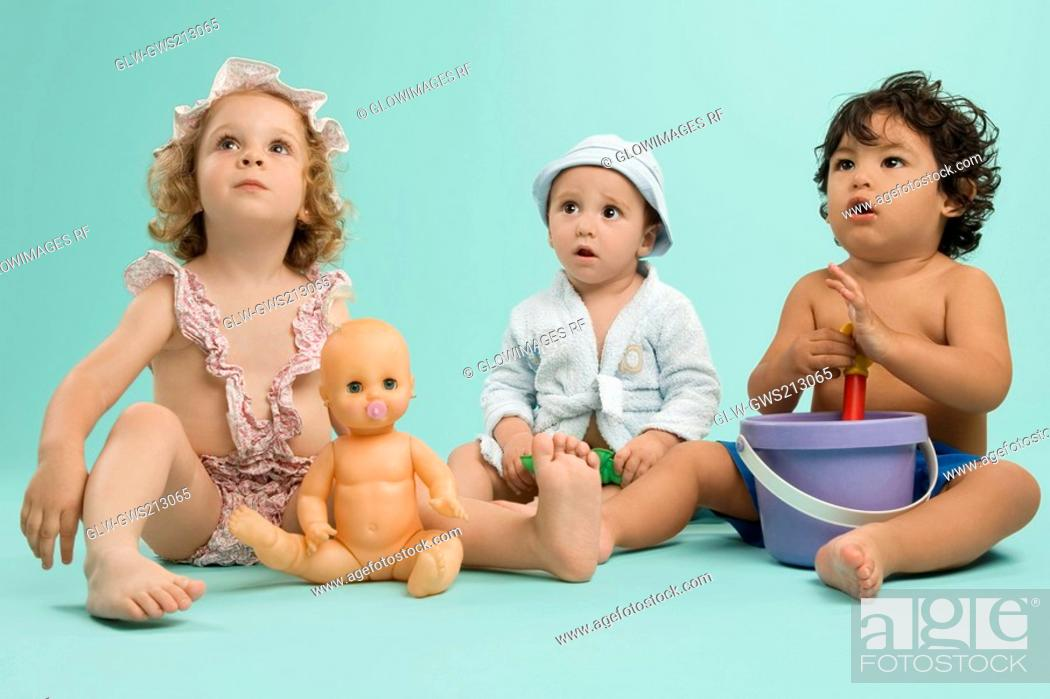 Stock Photo: Three children playing with toys.