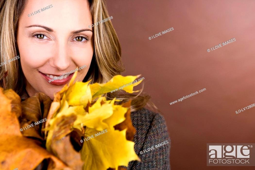 Stock Photo: A mid adult woman holding a handful of autumn leaves.