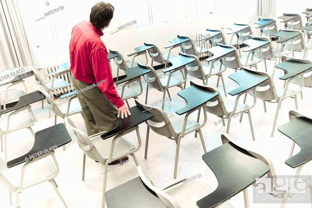 Stock Photo: Man standing among student desks in an empty college classroom.