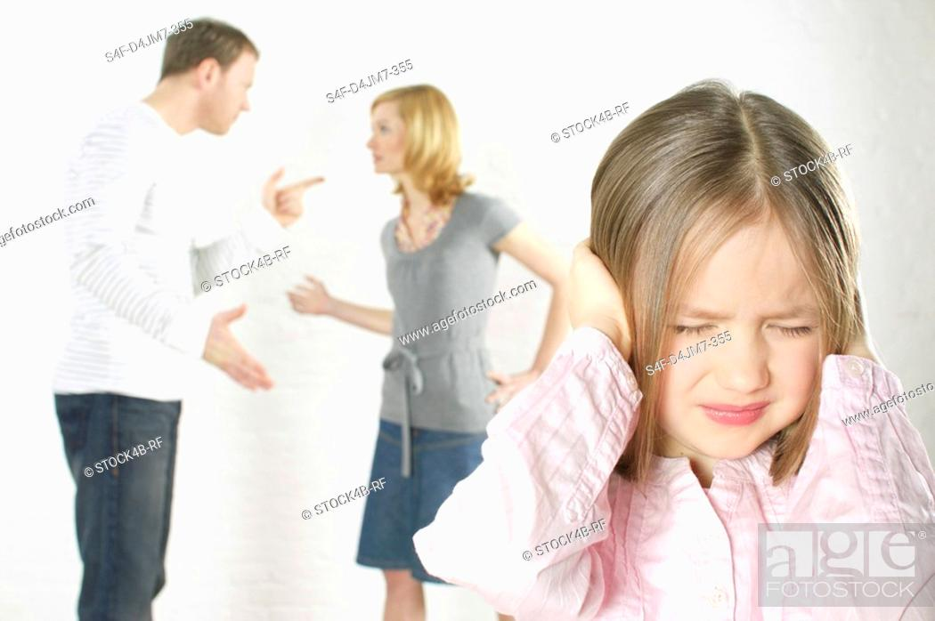 Stock Photo: Couple arguing, girl in foreground covering ears with hands.