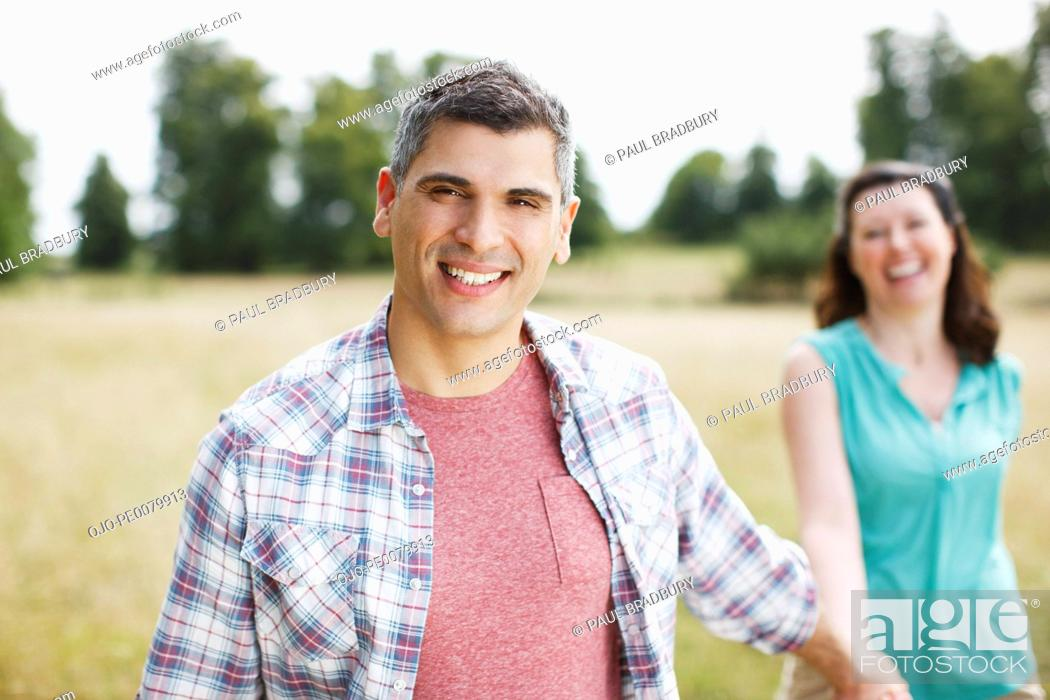 Stock Photo: Portrait of smiling couple holding hands in rural field.