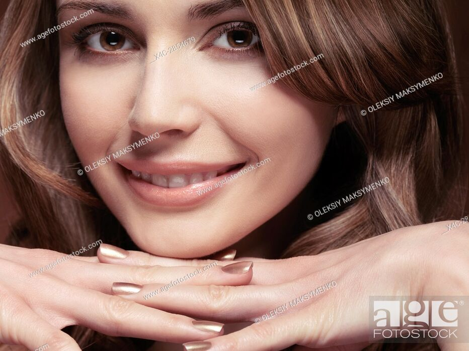 Stock Photo: Closeup beauty portrait of a beautiful smiling young caucasian woman resting her chin on her hands.