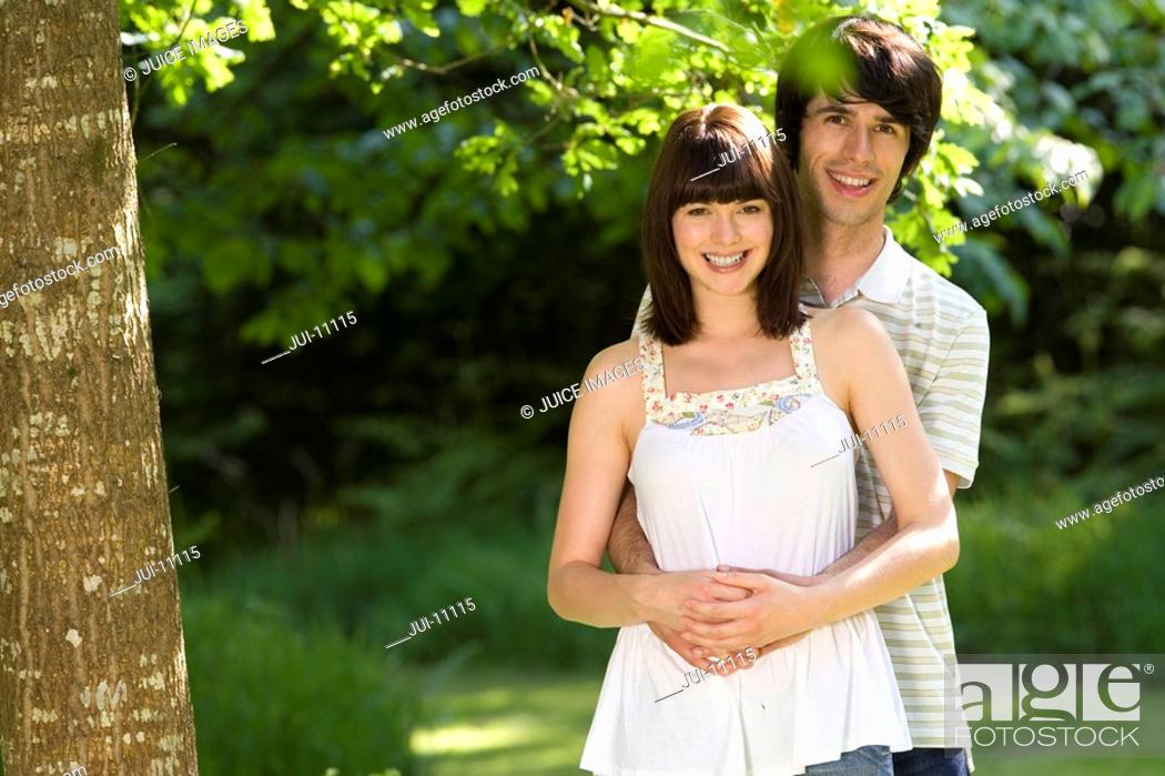 Stock Photo: Young couple outdoors, man embracing woman, smiling, portrait.