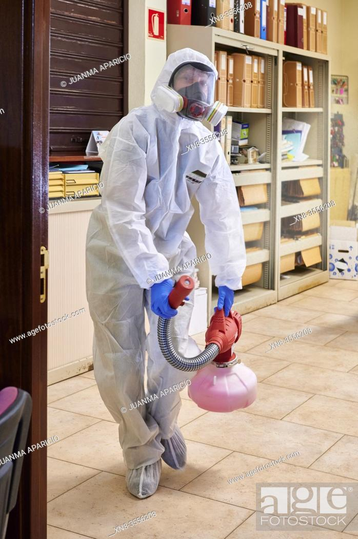 Stock Photo: Worker in protective suit disinfect interior office.