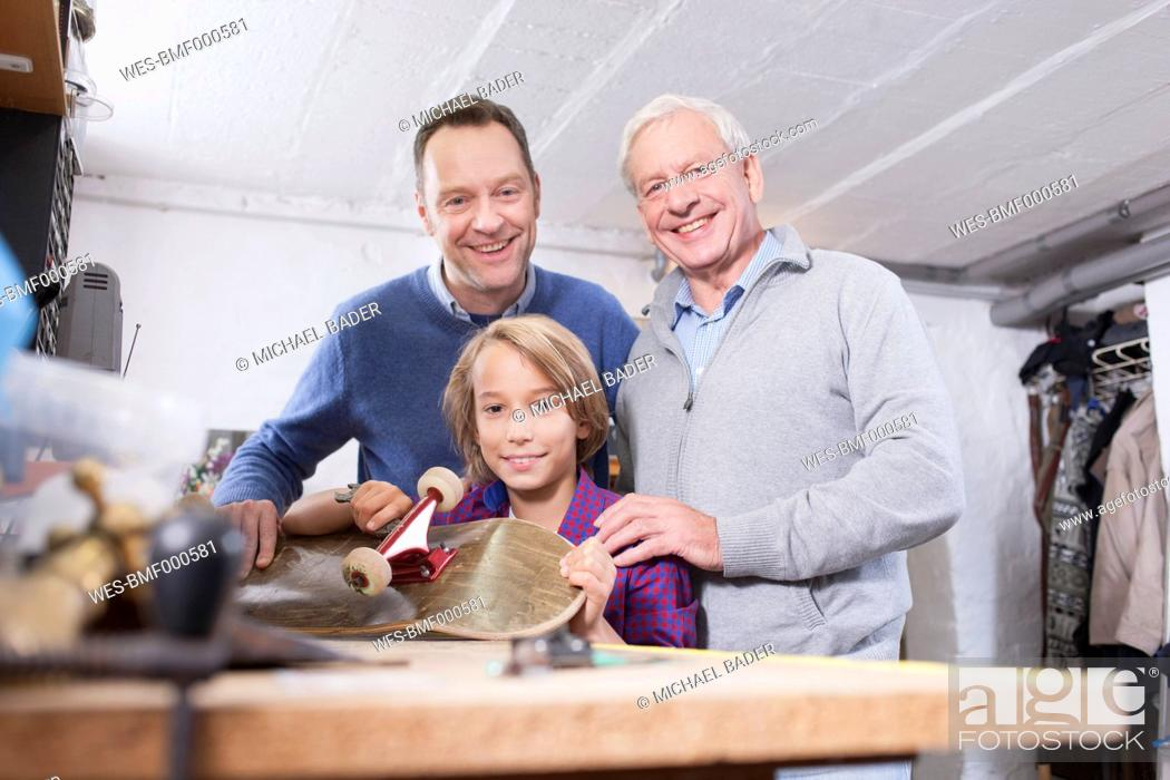 Stock Photo: Germany, Leipzig, Grandfather, father and son repairing skateboard.