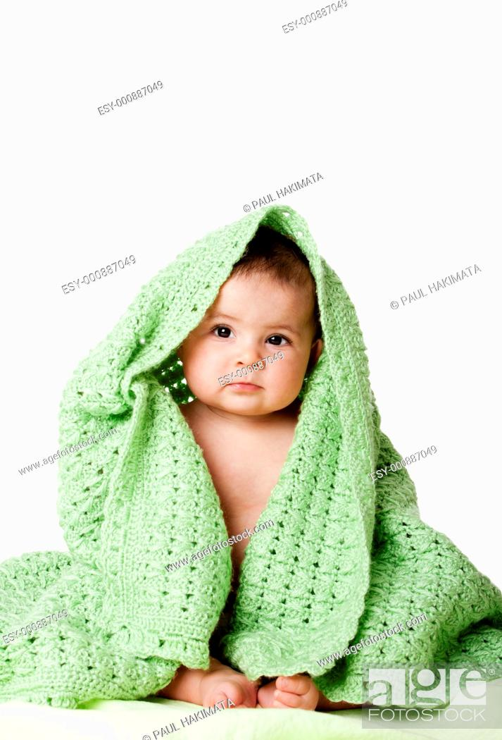 Stock Photo: Beautiful cute innocent Caucasian Hispanic baby face while sitting and covered between green knitted blankets, isolated.