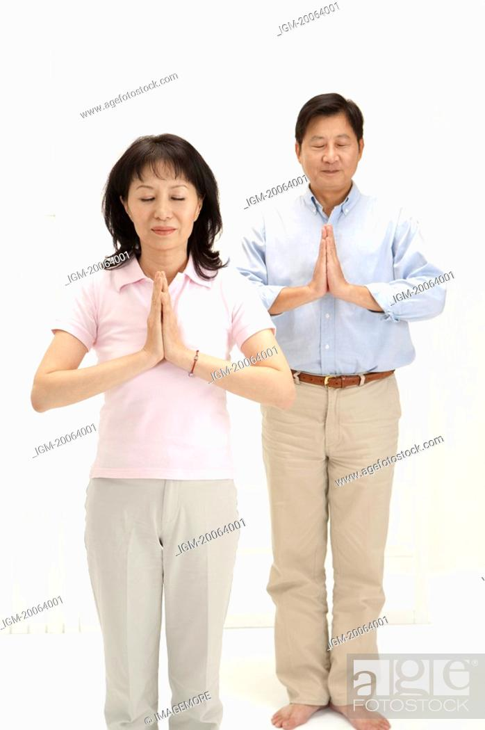 Stock Photo: Couple, Couple standing with hands praying and eyes closed.