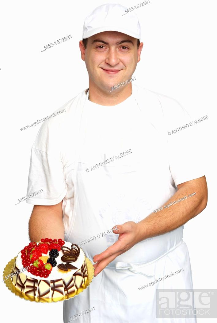 Stock Photo: An italian pastry cook show off his creation, a cake decorated with chocolate chips, whipped creap and fresh fruits.