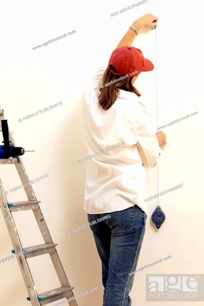 Stock Photo: Rear view of a young woman measuring a wall.