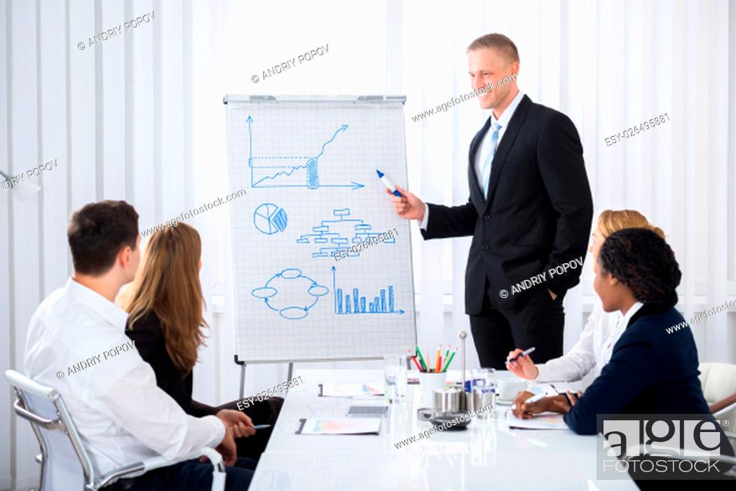 Stock Photo: Group Of Businesspeople Looking At Happy Businessman Explaining In Presentation.