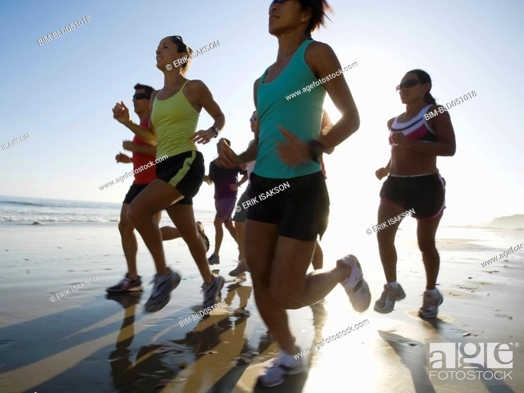 Stock Photo: Multi-ethnic runners racing at beach.