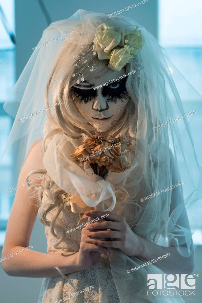 Photo de stock: Halloween witch. Beautiful bride woman wearing santa muerte mask and wedding dress holding dead bouquet of roses.