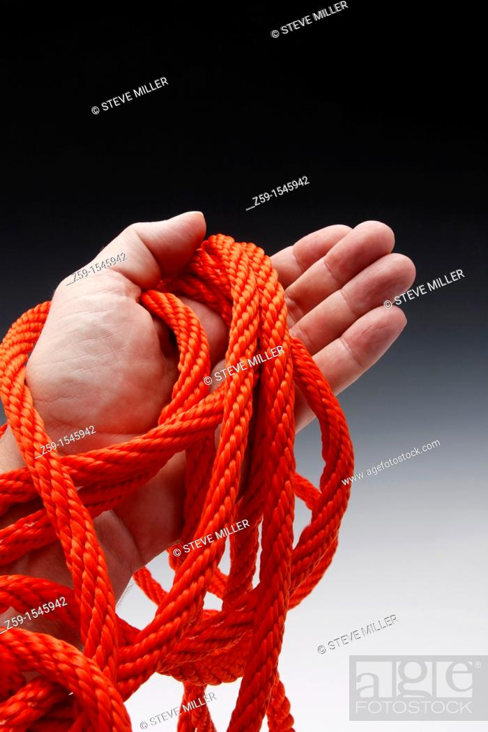 Stock Photo: hand clutching orange colored rope.