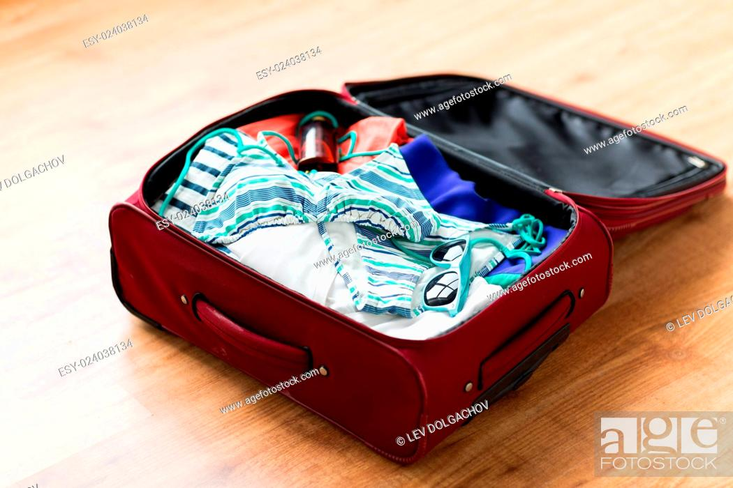 Stock Photo: summer vacation, travel, tourism and objects concept - close up of travel bag with beach clothes, sunglasses and sunscreen.