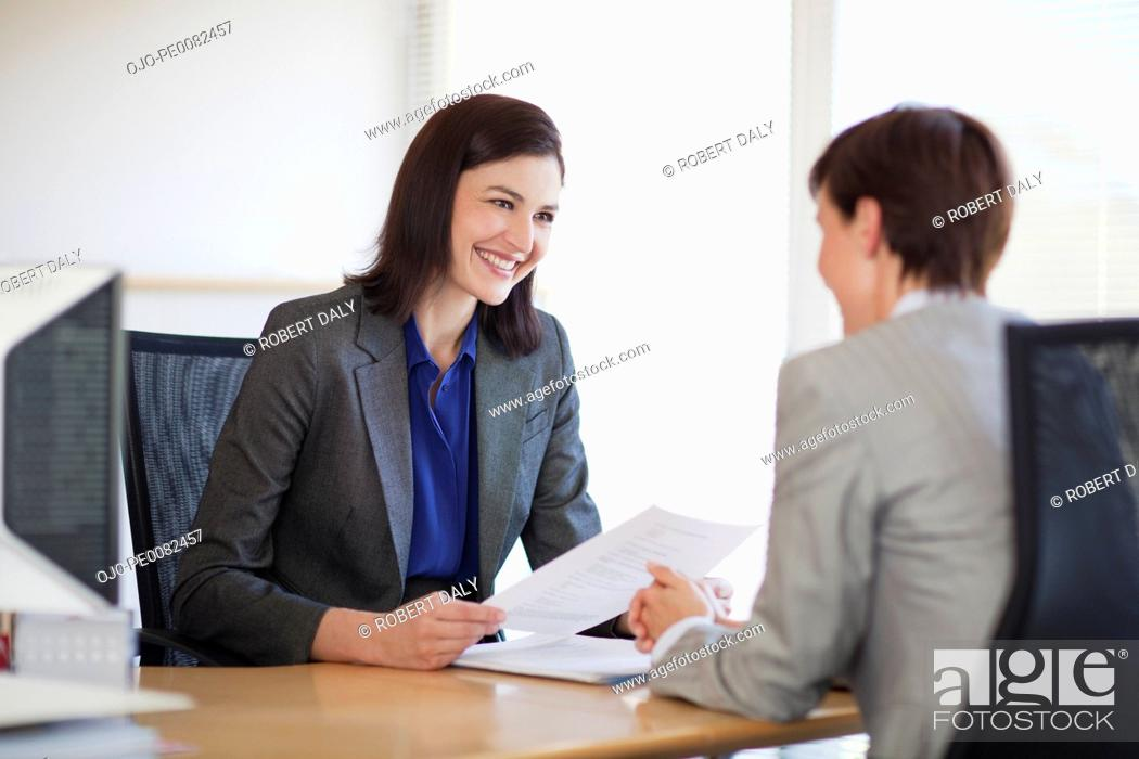 Stock Photo: Businesswomen with paperwork talking face to face.