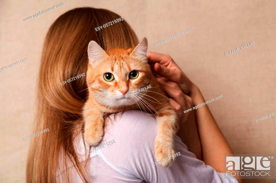 Stock Photo: Happy ginger tabby cat on the woman's shoulder. Beautiful striped red cat on the shoulder blonde, beige background.