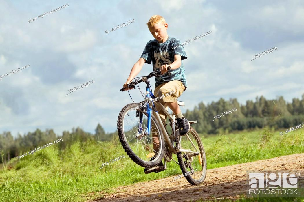 Stock Photo: Teenage Boy Riding Bicycle and Doing Action Trick.