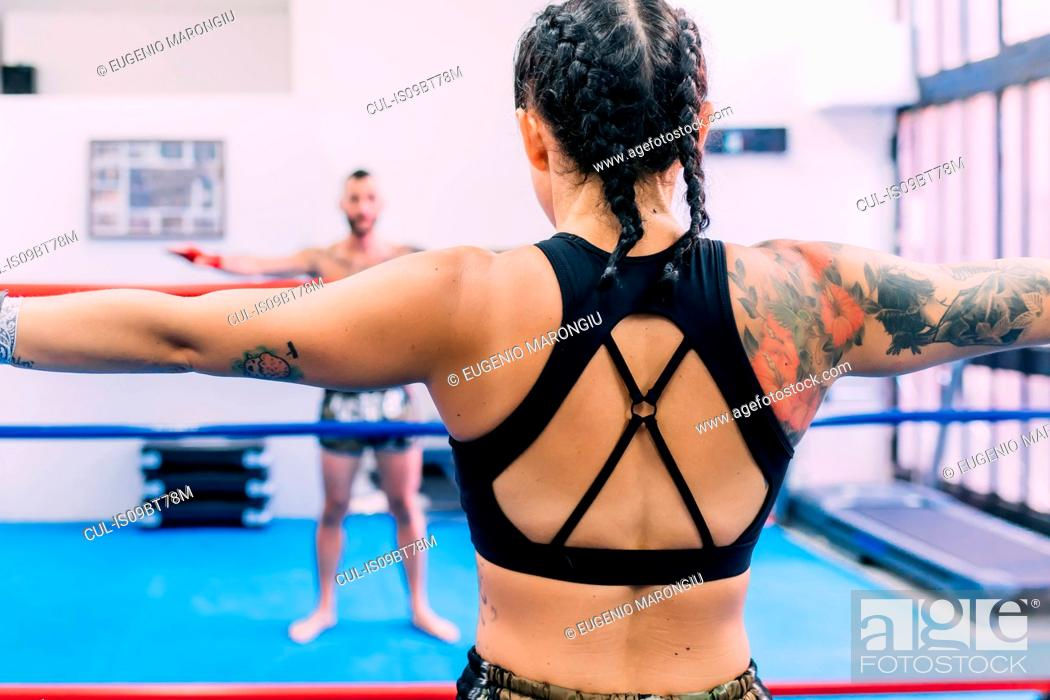 Stock Photo: Male and female boxers working out in boxing ring.