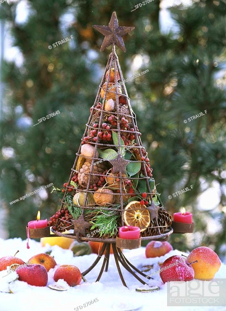 Stock Photo: Iron tree filled with fir cones, candles, fruit, berries.