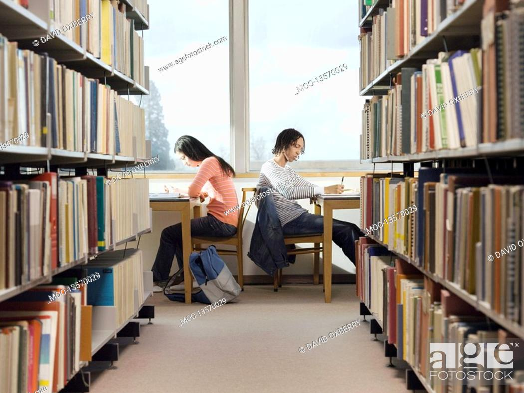 Stock Photo: Teenagers doing homework in library.