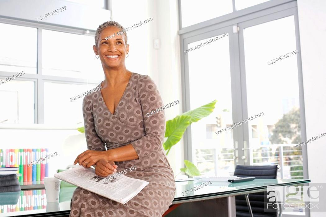Stock Photo: Businesswoman sitting on table with newspaper.