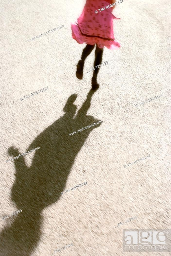 Stock Photo: Shadow, legs and lower body of 7 year girl running and wearing pink dress.