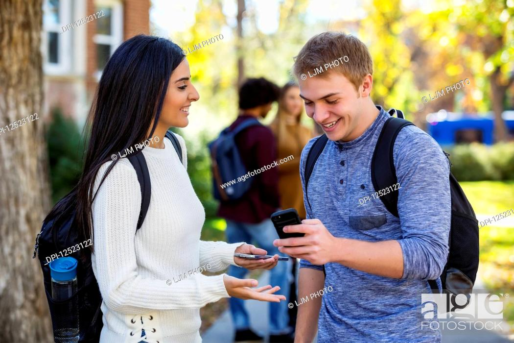 Stock Photo: A male and female university student stand on a path looking at a smart phone together, laughing and talking together with a small group of fellow students in.