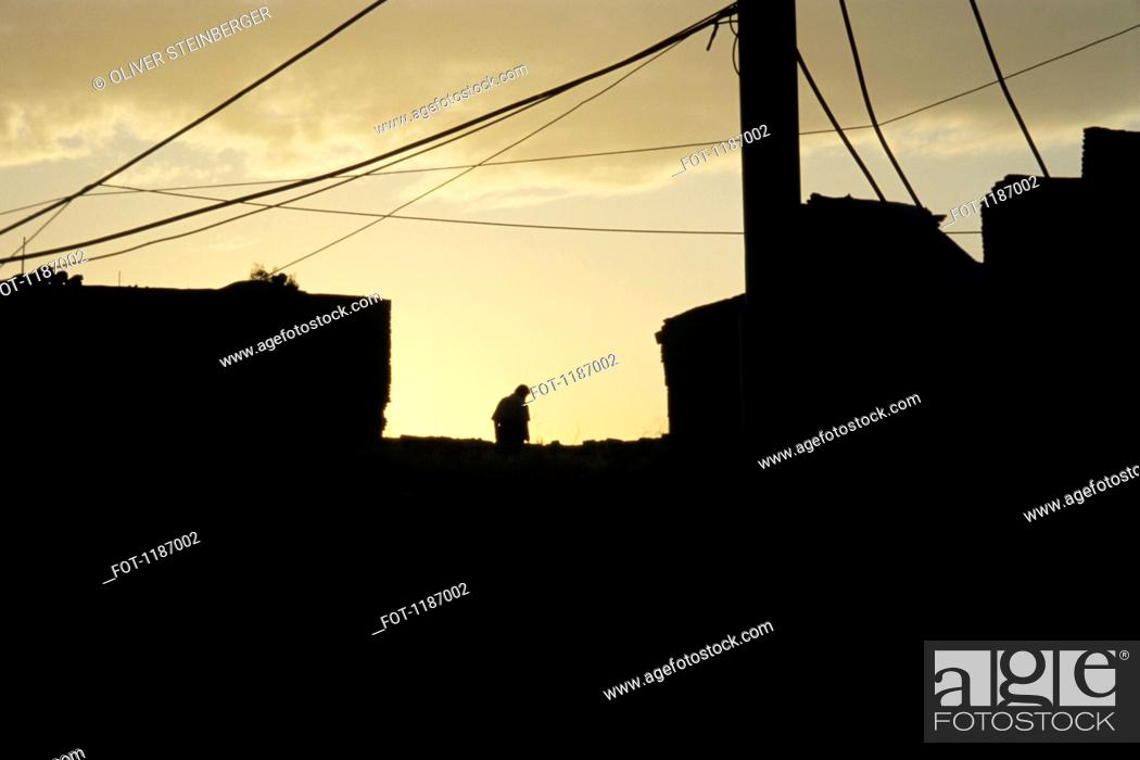 Stock Photo: Silhouetted man on roof top.