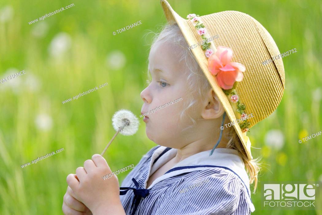 Stock Photo: Germany, Bavaria, Girl holding dandelion seed.