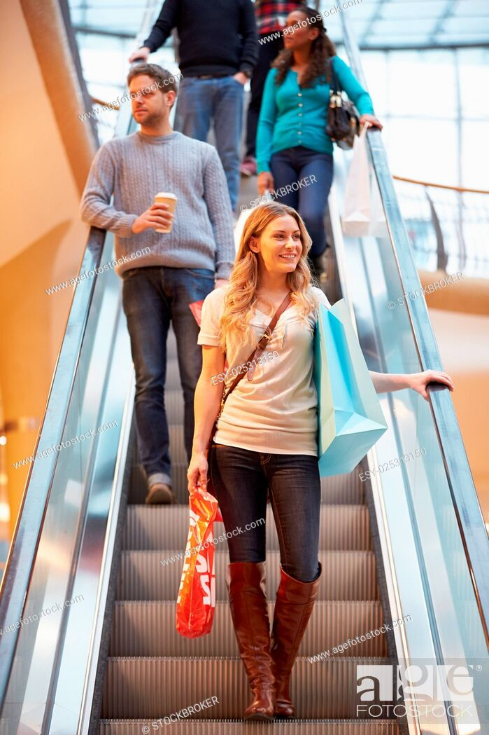 Stock Photo: Female Shopper On Escalator In Shopping Mall.