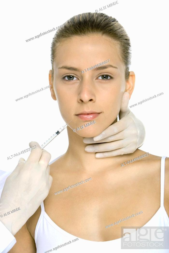 Stock Photo: Young woman receiving collagen injection, looking at camera.