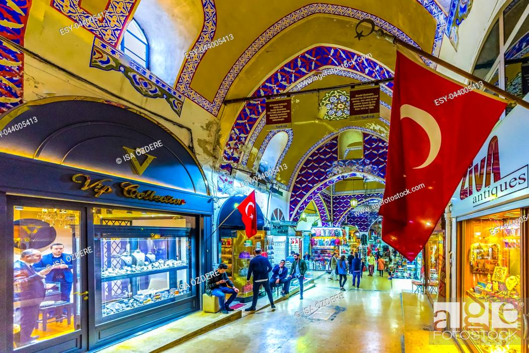 Imagen: Unidentified Tourists visiting and shopping in the Grand Bazaar in Istanbul. Interior of the Grand Bazaar with Turkish Flag on the foreground.