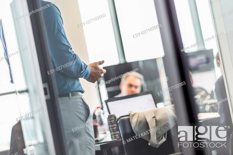 Stock Photo: Business man making a presentation at office. Business executive delivering a presentation to his colleagues during meeting or business training.