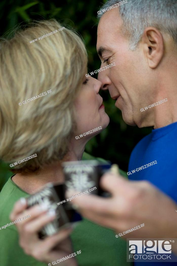 Stock Photo: Close-up of a senior man and a mature woman holding tea cups and kissing each other.