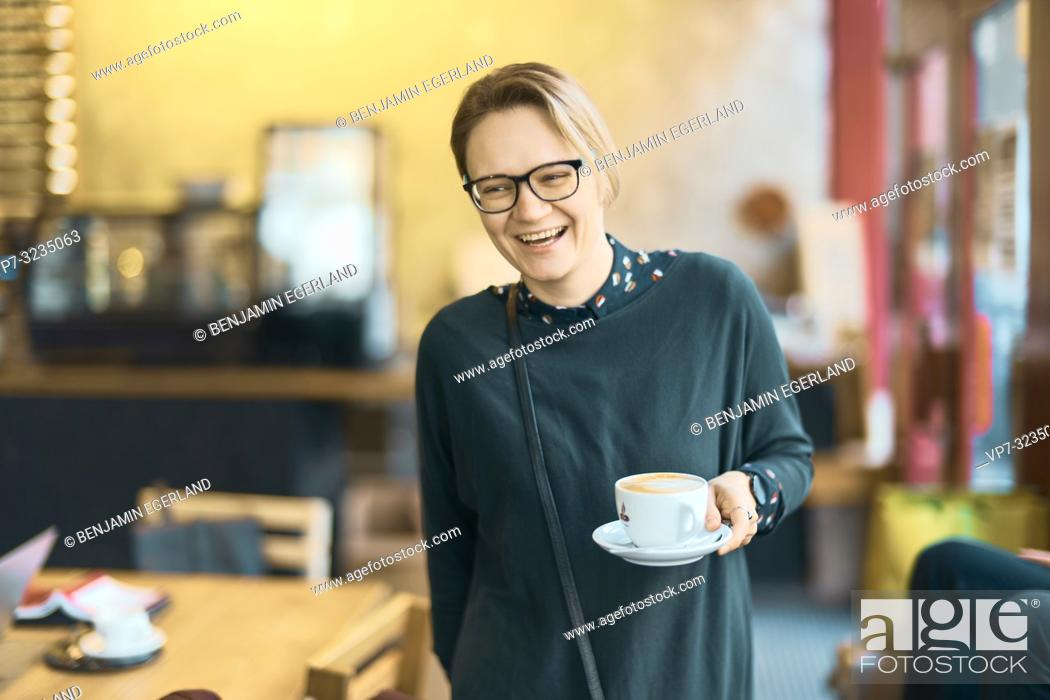 Photo de stock: laughing woman holding coffee cup indoors in café, happy, in Munich, Germany.